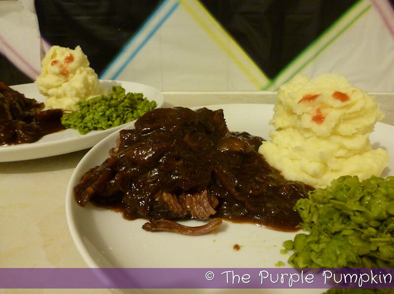 Beef stew on a white plate with mashed potatoes and peas.