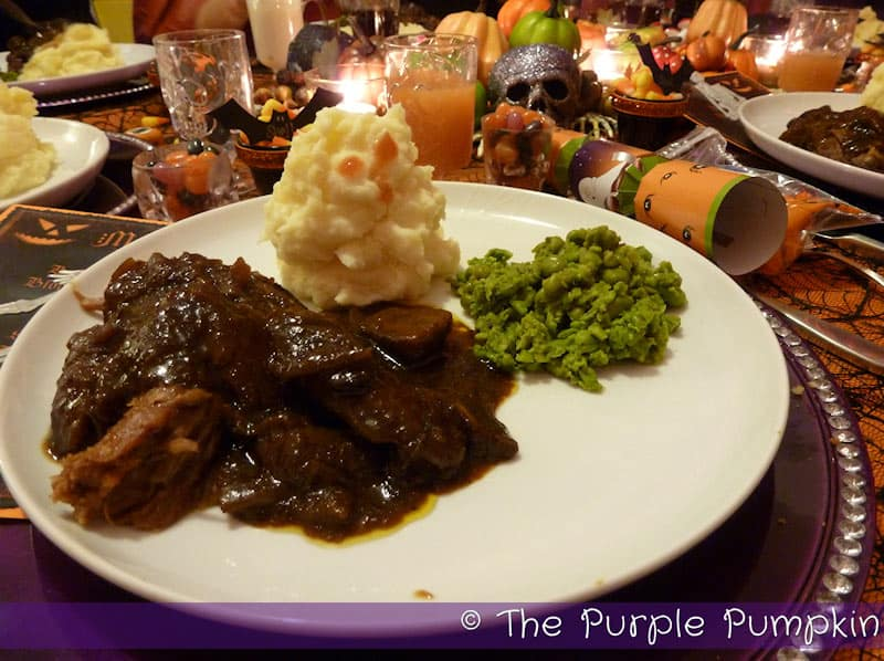 Beef stew with mashed potatoes and peas.