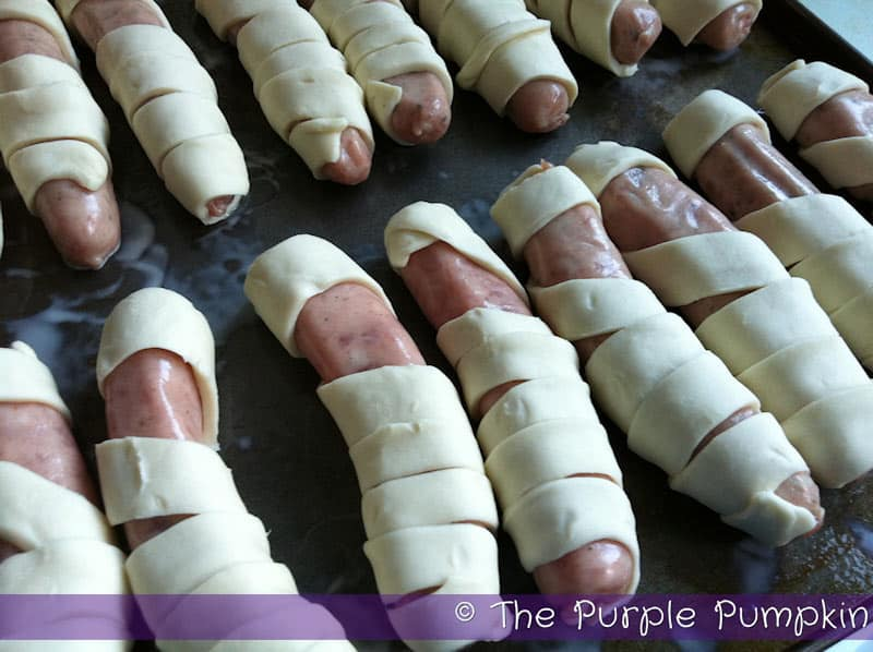 Puff pastry wrapped around chipolata sausages to make mummies for Halloween