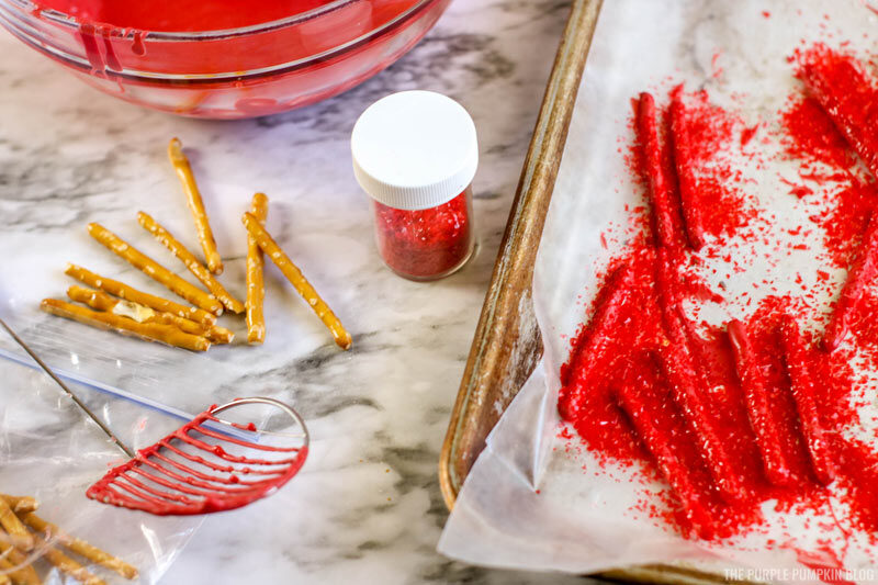 Dipping pretzel sticks into red candy melts
