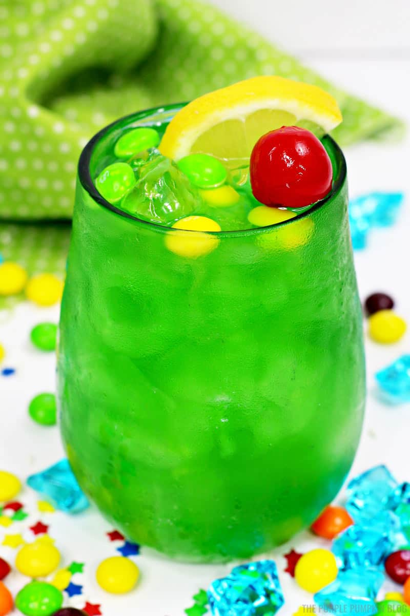 A glass of green drink decorated with a cherry and slice of lemon and green and yellow candies. Sitting on a white table with candies and crystals, and a green and white polka dot napkin in the background.