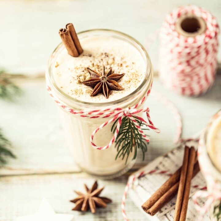A glass of eggnog with a cinnamon stick and star anise floating on top