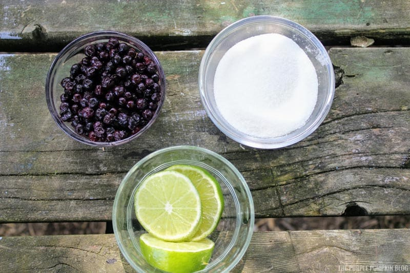 Blueberry Lime Mocktail ingredients - a bowl of blueberries, fresh lime, and sugar.