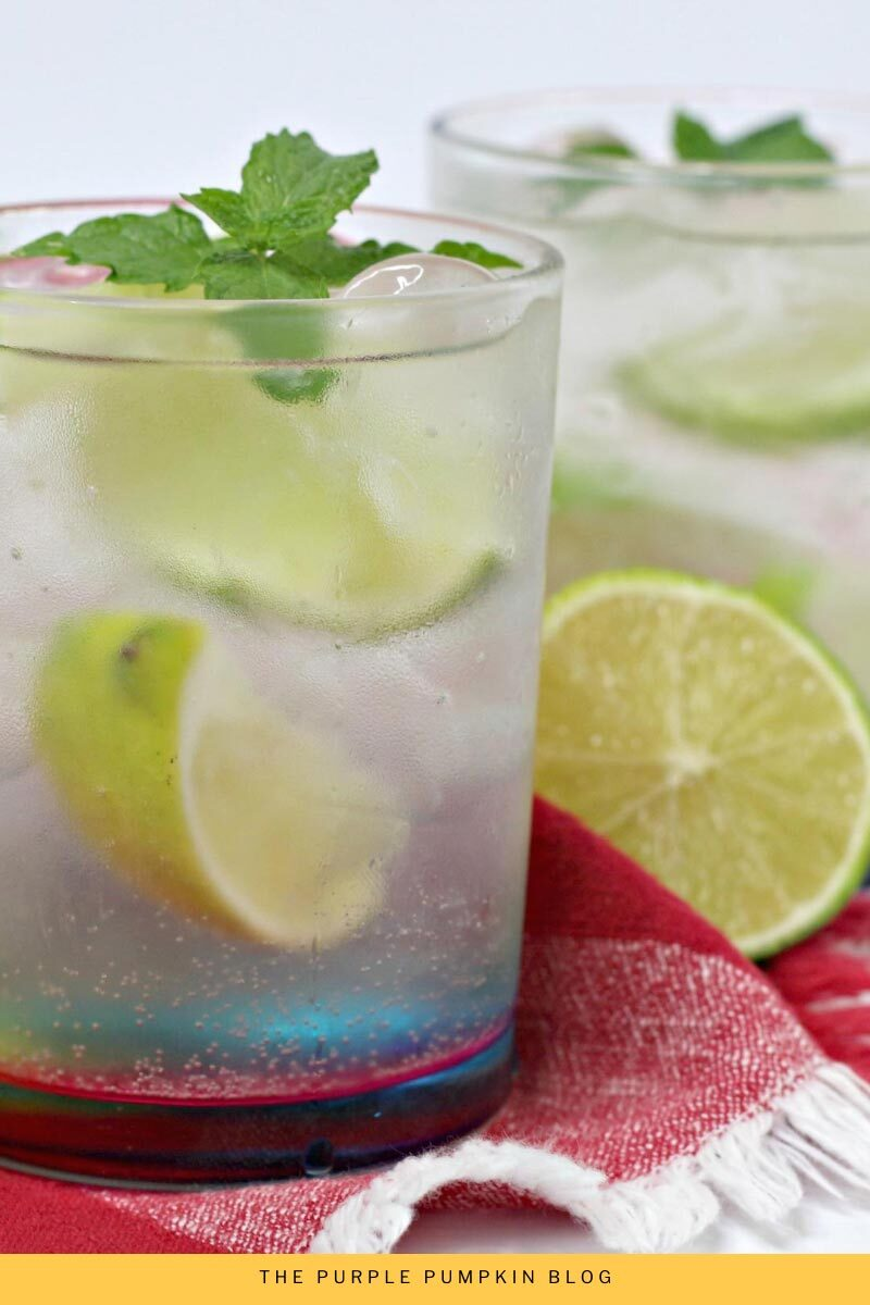 Two glasses of Brazilian Caipirinha Cocktail garnished with fresh mint and limes.
