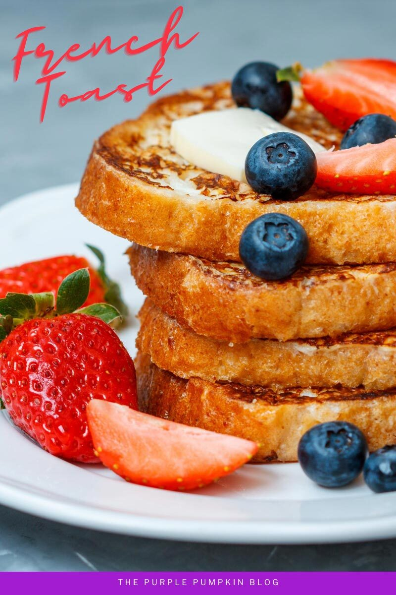 A stack of French Toast with a pat of butter, blueberries, and strawberries.