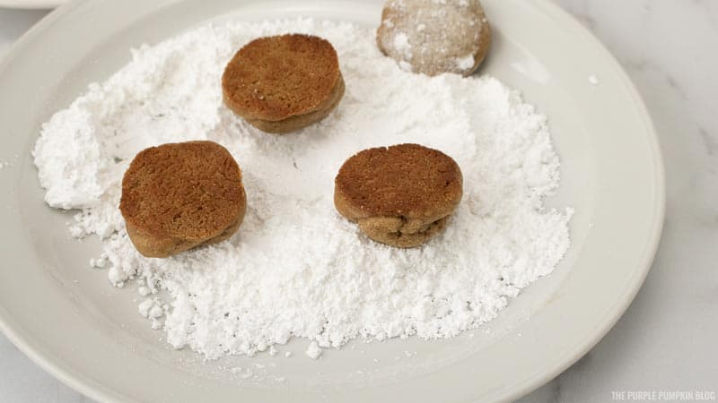 tossing cookies in powdered sugar