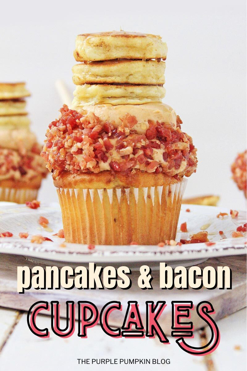 """A dingle cupcake sat on a white plate, topped with frosting covered in bacon bits, with a mini stack of pancakes sat on top drizzled with syrup. Text overlay says""""Pancakes & Bacon Cupcakes"""""""