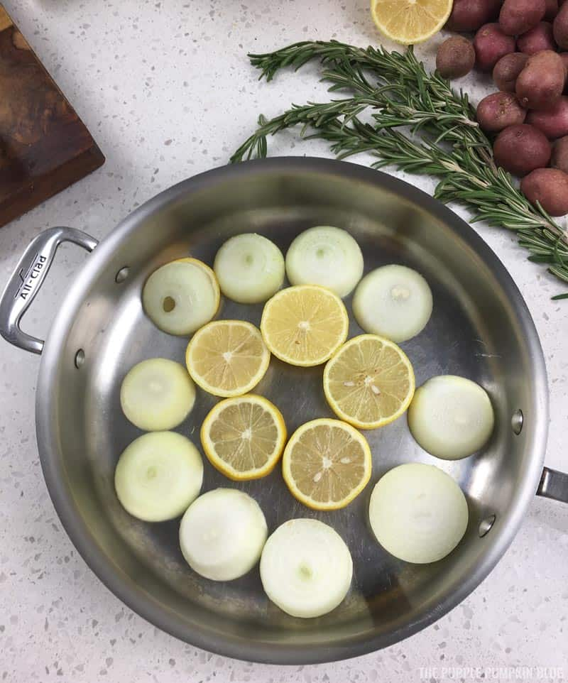 Slices of lemon and onion in bottom of roasting pan