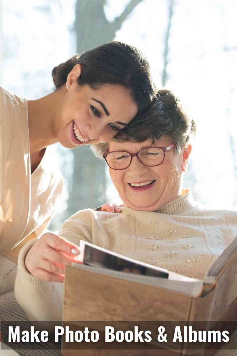 An elderly woman and a younger woman smiling as they look through a photo album