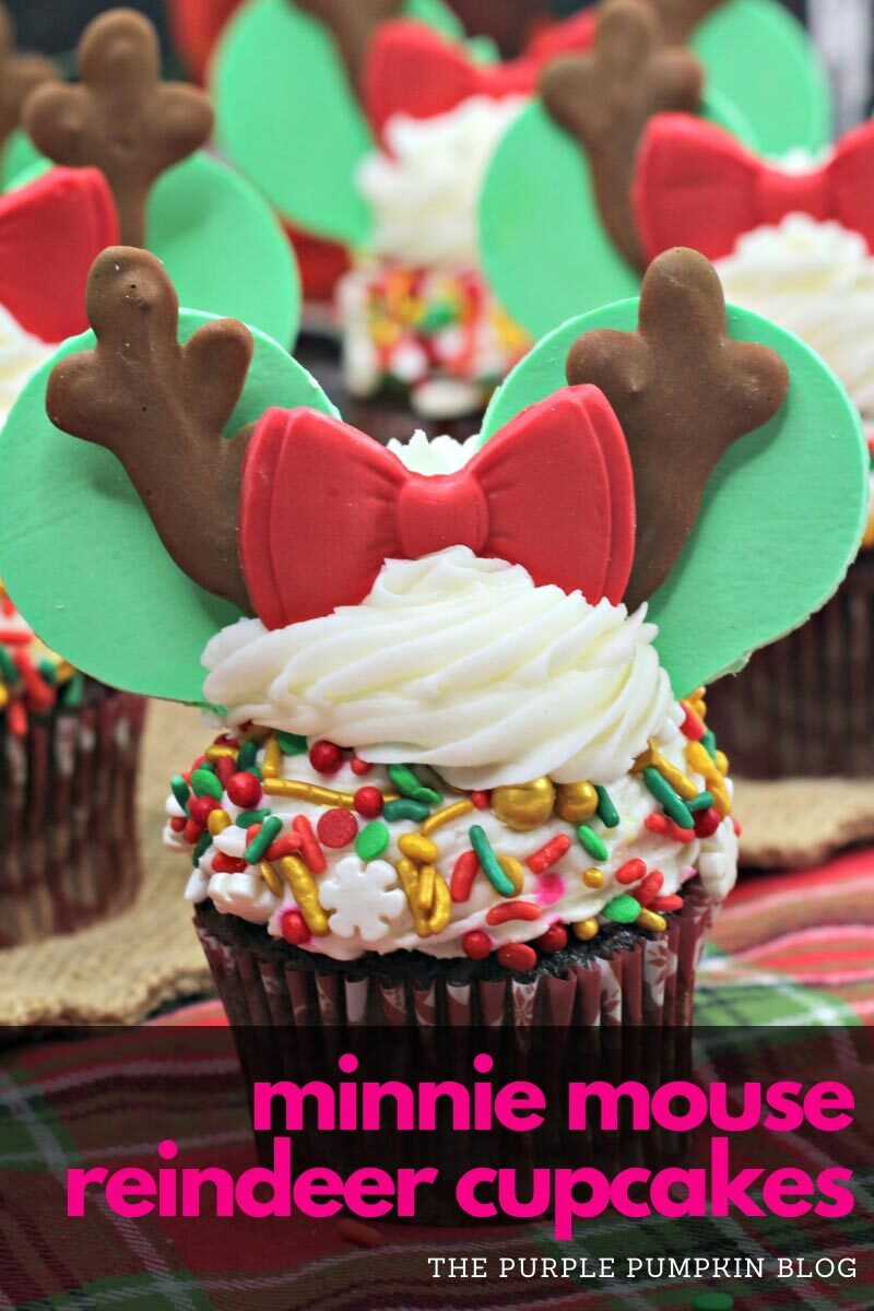 """A chocolate cupcake topped with frosting and covered green, red, gold, and white sprinkles. With another swirl of frosting on top. Inserted into the frosting are green Minnie""""ears"""", reindeer antlers and a red bow all made from fondant. Text overlay says""""Minnie Mouse Reindeer Cupcakes"""". Same cupcake featured throughout with different text overlay, unless otherwise described."""