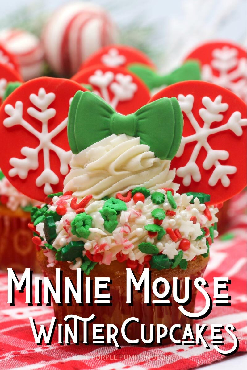"Cupcake topped with white frosting covered in green and red festive sprinkles with a swirl of frosting on top. Red fondant""ears"" with piped snowflakes are inserted into the sides of the frosting with a green fondant bow in the front. Text overlay says""Minnie Mouse Winter Cupcakes"". Same cupcake featured throughout with different text overlay unless otherwise described."