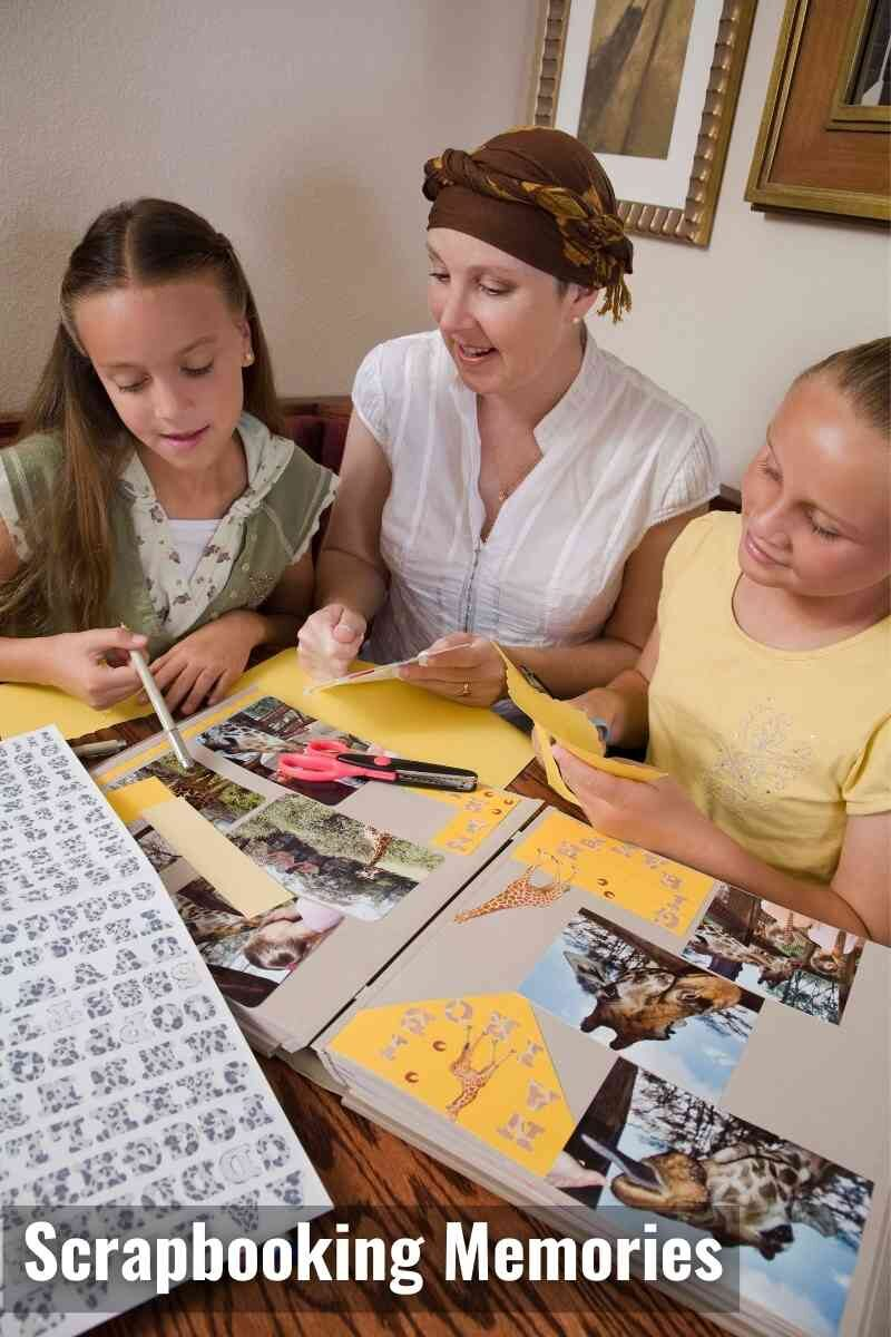 A mother and two children sat at a table making a scrapbook of photographs.