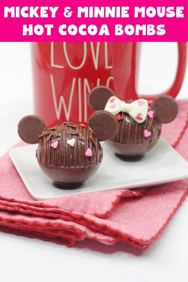 """Two hot chocolate bombs - one decorated like Minnie Mouse, and the other like Mickey Mouse. Sat on a white plate on a red cloth with a red mug in the background. Text overlay says""""Mickey & Minnie Hot Cocoa Bombs"""". Similar photos of the recipe from various angles are used throughout but with different text overlays unless otherwise described."""