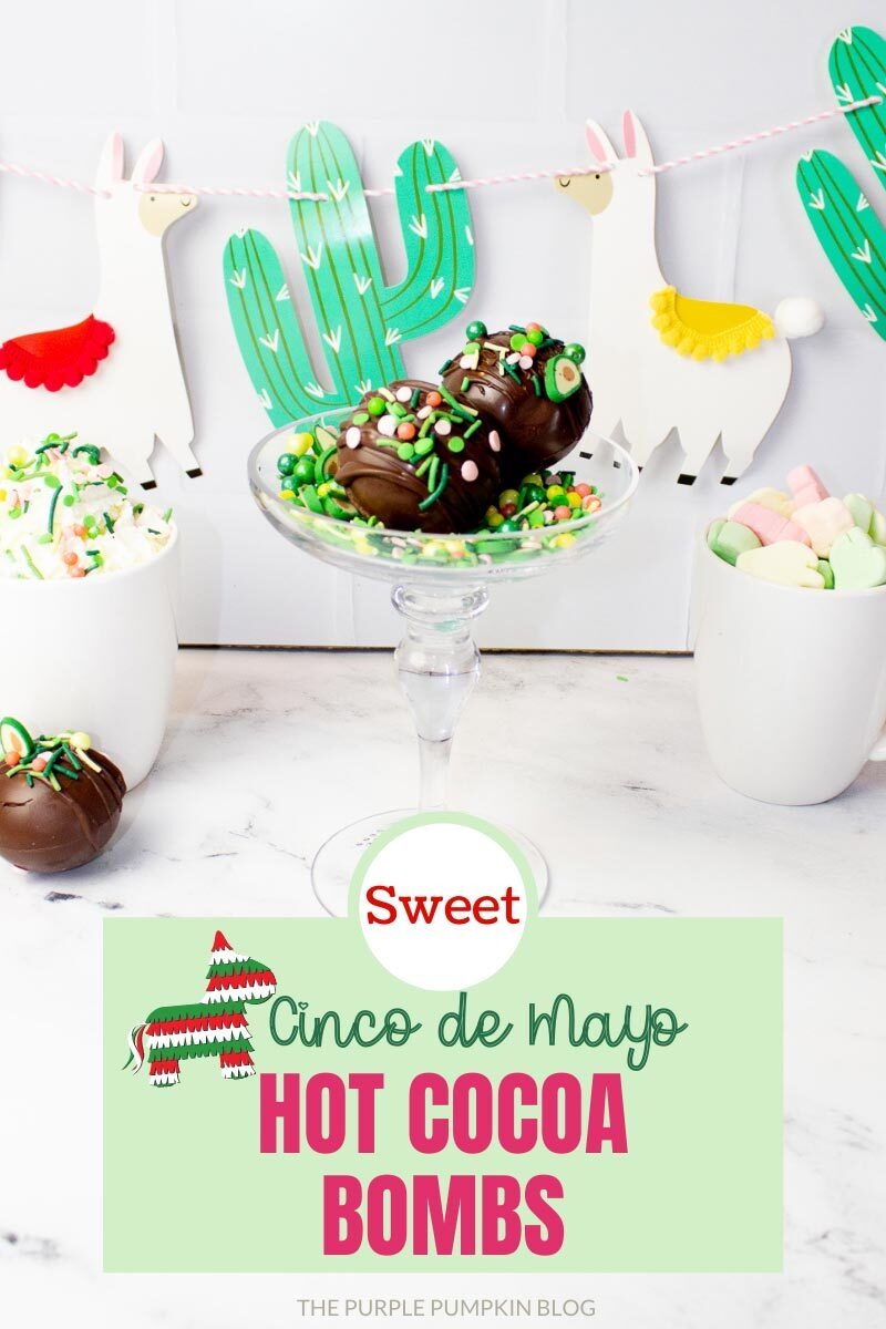 "Hot cocoa bombs covered with avocado-shaped sprinkles displayed in a cocktail glass, with two mugs of hot chocolate on either side. A llama and cactus banner hangs in the background. Text overlay says""Sweet Cinco de Mayo Hot Cocoa Bombs"". Similar photos of the recipe from various angles are used throughout but with different text overlays unless otherwise described."